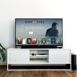 tv on white tv stand with gone girl on background