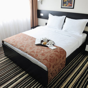 hotel room bed with breakfast tray on bed