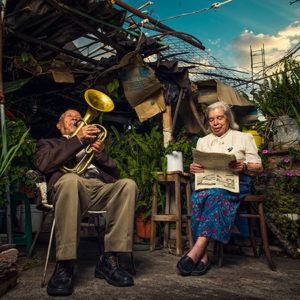 old couple in house without a roof man playing trombone woman reading